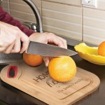 Engraved Cutting Board with knife cutting orange
